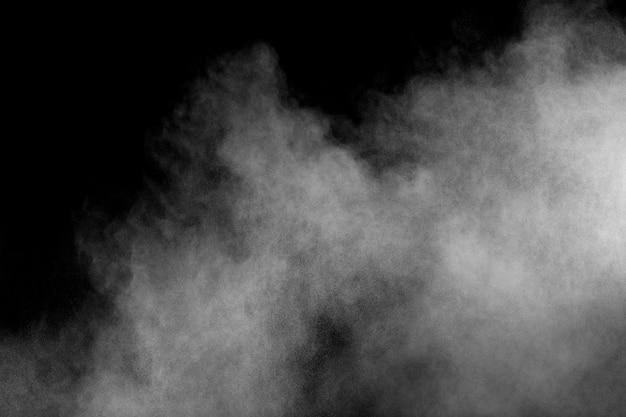 Esplosione di polvere bianca isolato su priorità bassa nera. spruzzata di particelle di polvere bianca. Foto Premium
