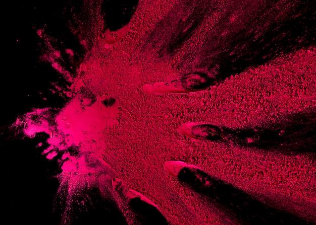 Esplosione di polvere di colore rosa astratto su sfondo nero Foto Gratuite