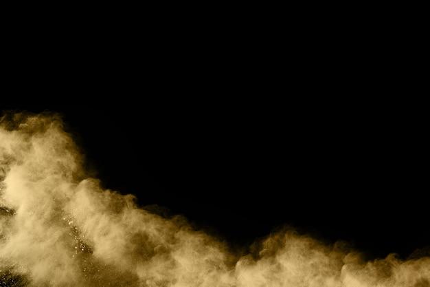Esplosione di polvere dorata su sfondo nero. blocca il movimento. Foto Premium