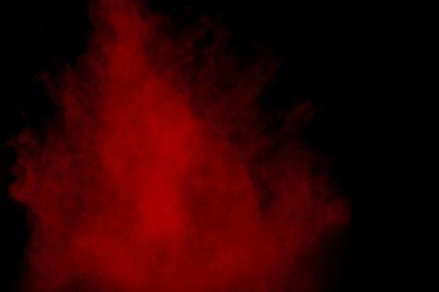 Esplosione di polvere rossa su nero Foto Premium
