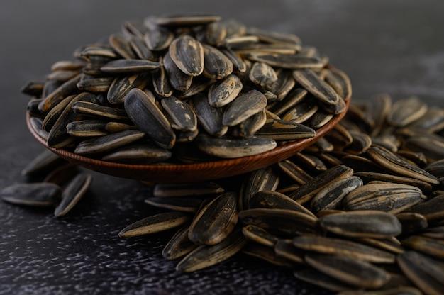 Esponga al sole il seme di fiore in una ciotola di legno sul pavimento nero del cemento. Foto Gratuite