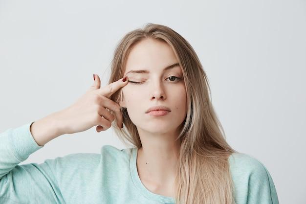 Espressioni del viso umano giovane bella donna premurosa con capelli lisci tinti di biondo in maglione a maniche lunghe azzurro che tocca con l'occhio di dito Foto Gratuite