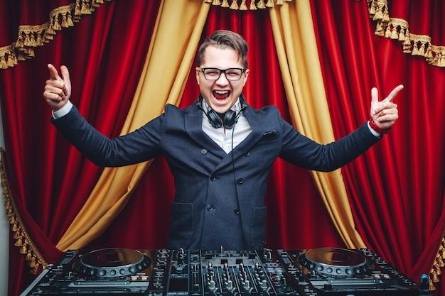 Espressivo dj alla moda in tuta blu al lavoro solleva le mani su uno sfondo rosso Foto Premium