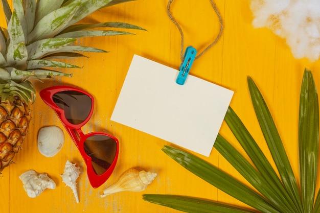 Estate con conchiglie, bicchieri, frutta e carta su un giallo Foto Gratuite