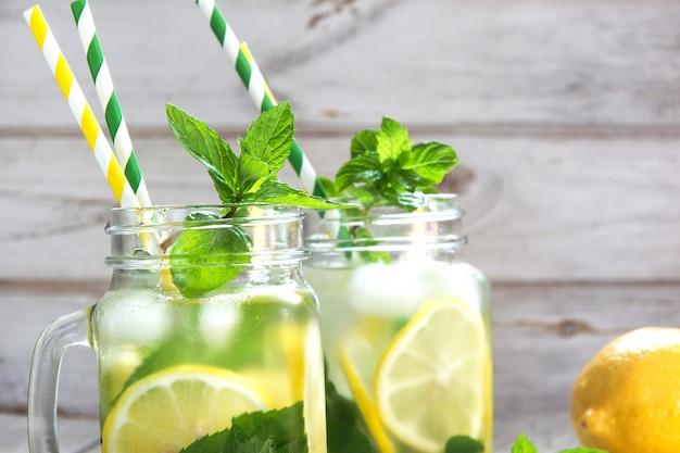 Estate rinfrescante acqua con limone, menta e ghiaccio in barattolo di vetro su un fondo di legno bianco. Foto Premium