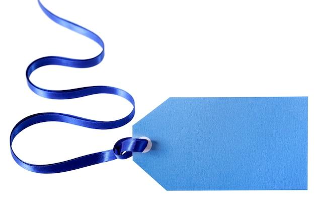 Etichetta regalo blu chiaro o biglietto di prezzo con nastro blu profondo isolato su bianco Foto Gratuite