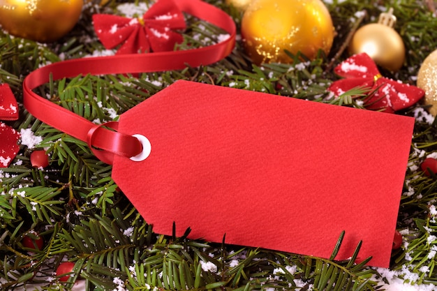 Etichetta regalo rosso o biglietto di prezzo con nastro rosso su uno sfondo di albero di natale Foto Premium