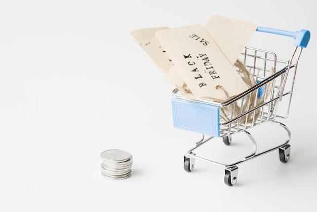 Etichette nel carrello vicino a monete Foto Gratuite