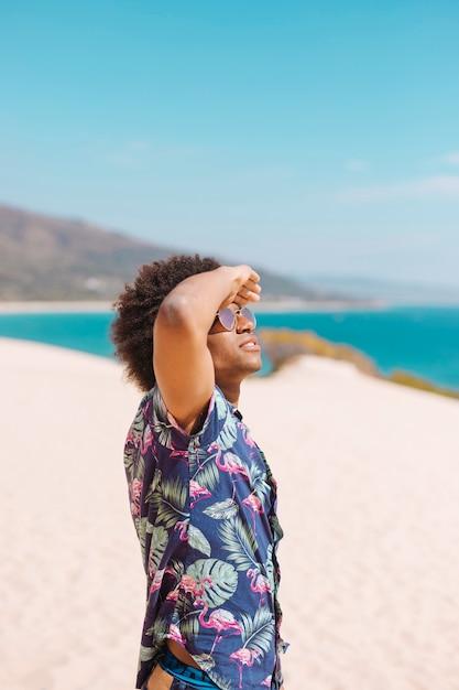 Etnico maschio guardando il cielo sulla spiaggia Foto Gratuite