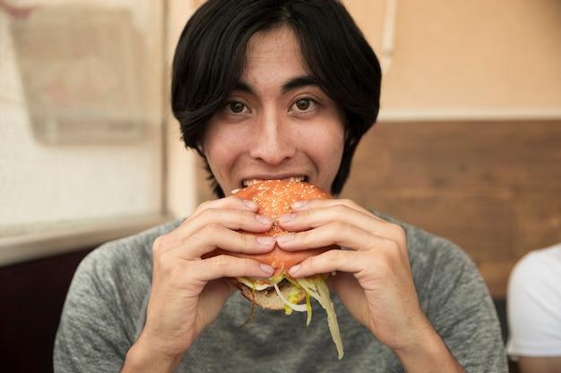 Etnico maschio mangiando hamburger e guardando la fotocamera Foto Gratuite