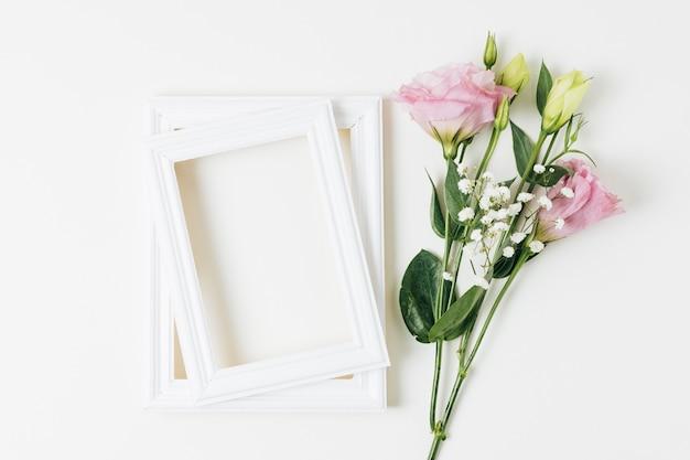 Eustoma e fiori del respiro del bambino vicino al telaio in legno su sfondo bianco Foto Gratuite