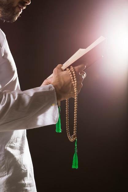 Evento del ramadam e uomo arabo che tiene il corano e le perle di preghiera Foto Gratuite