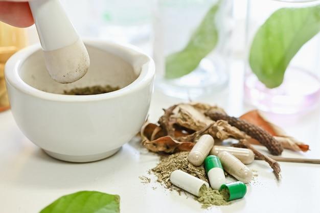 Fabbricazione della medicina di erbe del primo piano, macinazione della mano, medicina di erbe in mortaio Foto Premium