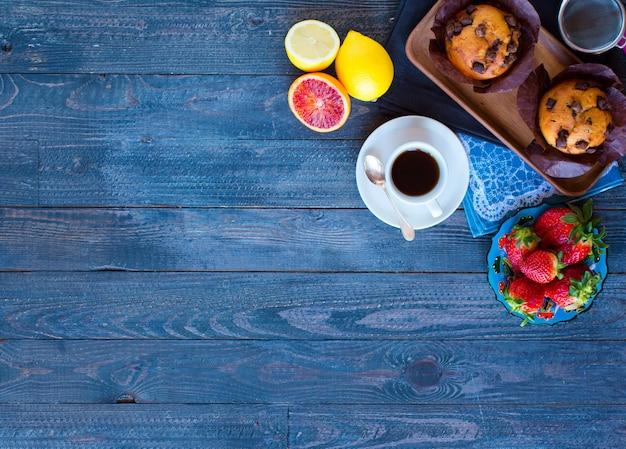Faccia colazione con caffè e tè con differenti pasticcerie e frutti su una tavola di legno Foto Premium