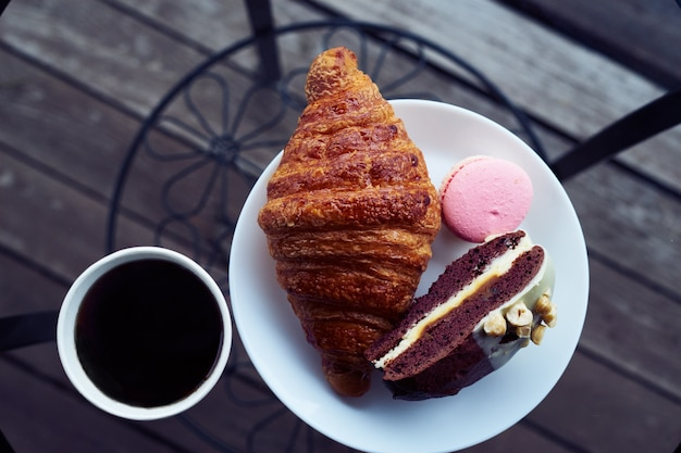 Faccia colazione con il croissant e dessert, caffè o tè in tazza di plastica, nel villaggio, all'aperto, natura. Foto Premium