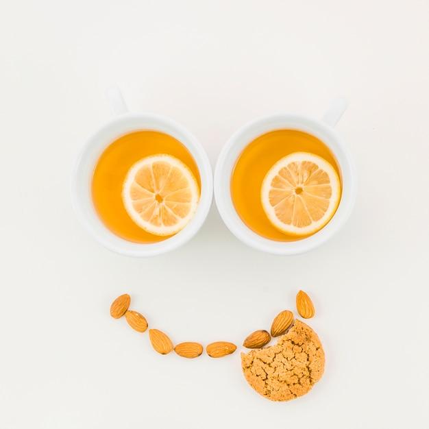 Faccia felice fatta con tazza di tè al limone; mandorle e biscotti mangiati su sfondo bianco Foto Gratuite