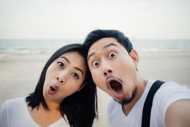 Faccia scossa del turista delle coppie sul viaggio di vacanza romantica della spiaggia. Foto Premium