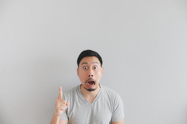Faccia scossa dell'uomo in maglietta grigia con punto della mano su spazio vuoto. Foto Premium