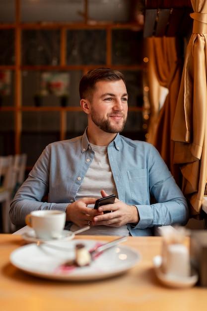 Faccina al ristorante con il telefono Foto Gratuite