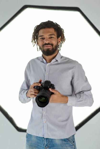 Faccina che tiene la macchina fotografica Foto Gratuite