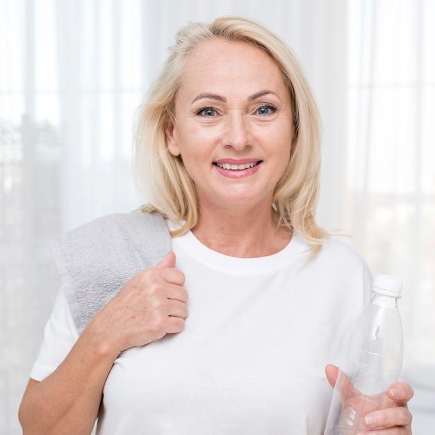 Faccina di tiro medio donna con asciugamano e bottiglia d'acqua Foto Gratuite