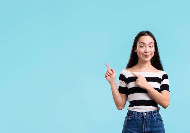 Faccina femminile che punta con copia-spazio Foto Gratuite