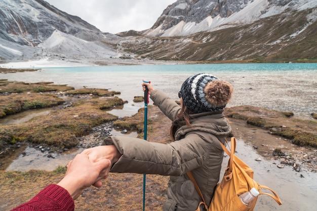 Facendo un'escursione del viaggiatore giovane delle coppie che sembra bello paesaggio nel lago del latte nella riserva naturale di yading Foto Premium