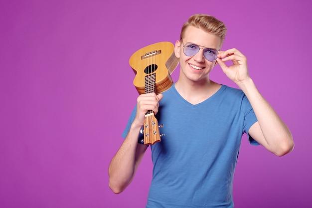 Fachion bellezza uomo divertente con ukulele nelle mani su sfondo viola copyspace Foto Premium