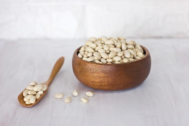 Fagioli bianchi crudi in una ciotola di legno e cucchiaio su una tavola bianca Foto Premium