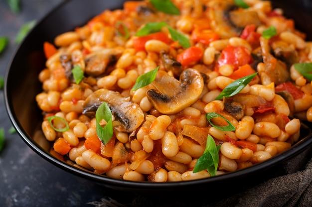 Fagioli bianchi in umido con funghi e pomodori con salsa piccante in una ciotola nera. Foto Premium