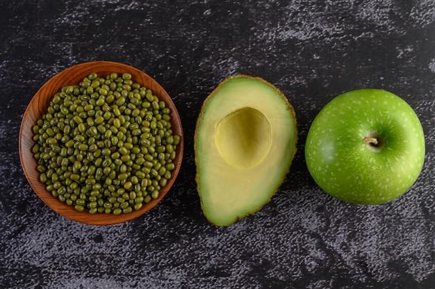 Fagiolo verde, avocado e mela su un pavimento di cemento nero. Foto Gratuite