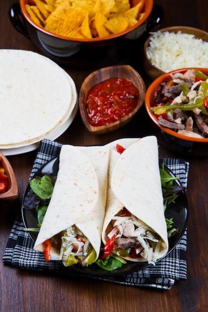 Fajitas di pollo e manzo fatte in casa con verdure e tortillas Foto Premium