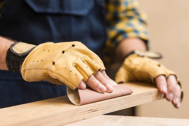 Falegname maschio che liscia la plancia di legno con carta vetrata Foto Gratuite
