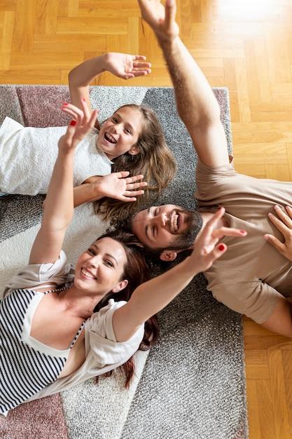 Famiglia adorabile che si trova sul pavimento Foto Gratuite