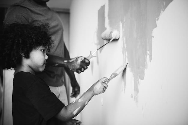 Famiglia africana che dipinge la parete della casa Foto Gratuite