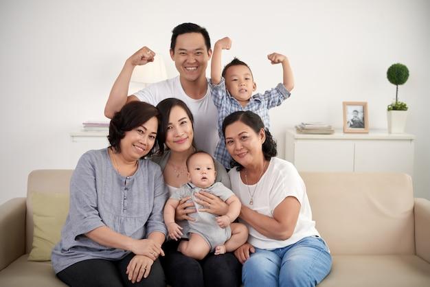 Famiglia allargata asiatica con il bambino e il bambino che posano insieme intorno allo strato a casa Foto Gratuite