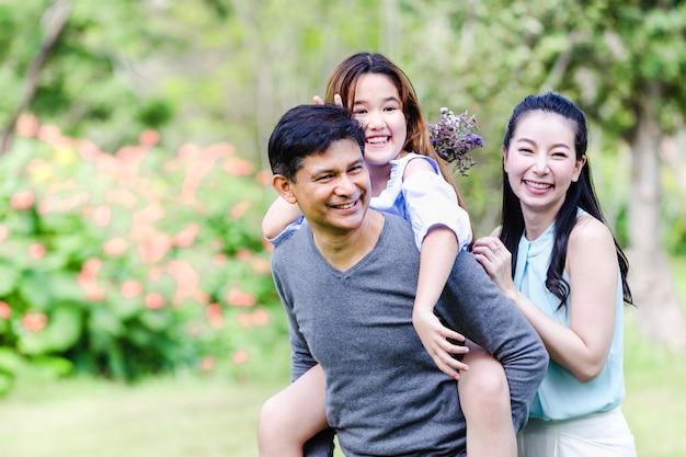 Famiglia allegra che ha picnic che si rilassa insieme sulla natura verde in parco Foto Premium