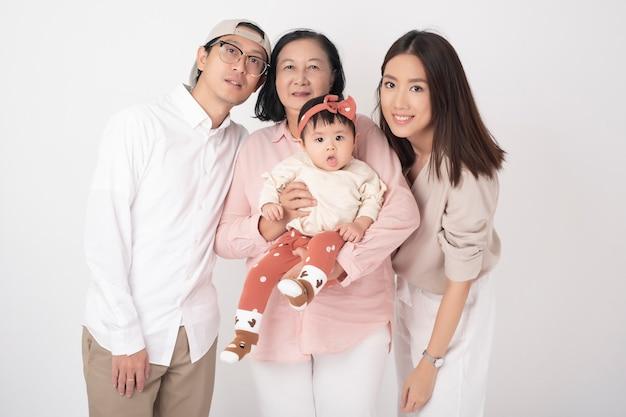 Famiglia asiatica felice sulla parete bianca Foto Premium