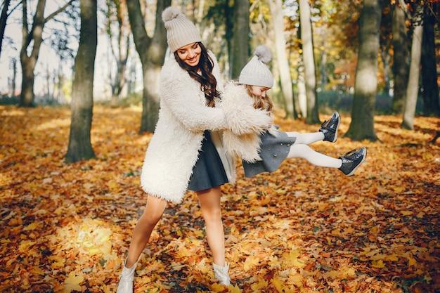 Famiglia carina ed elegante in un parco in autunno Foto Gratuite
