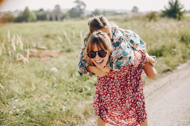 Famiglia carino ed elegante in un campo estivo Foto Gratuite
