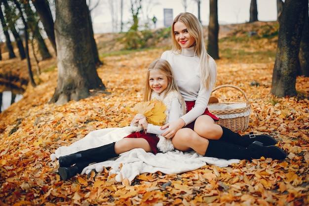 Famiglia carino ed elegante in un parco d'autunno Foto Gratuite
