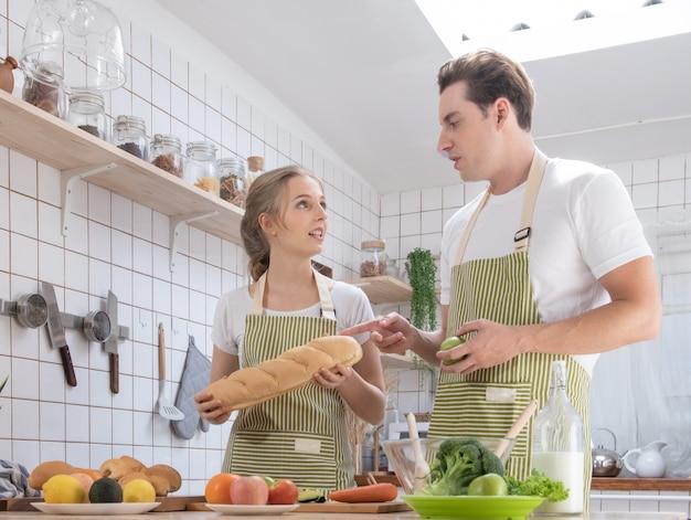 Famiglia caucasica felice delle coppie che cucina nella cucina moderna a casa con amore. uomo e donna romantici sposati che cucinano l'insalata della verdura fresca concetto sano di stile di vita. Foto Premium