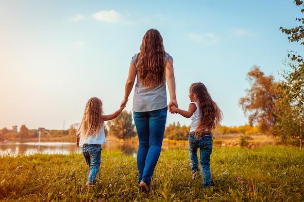 Famiglia che cammina dal fiume di estate al tramonto. madre e le sue figlie divertirsi all'aperto. Foto Premium