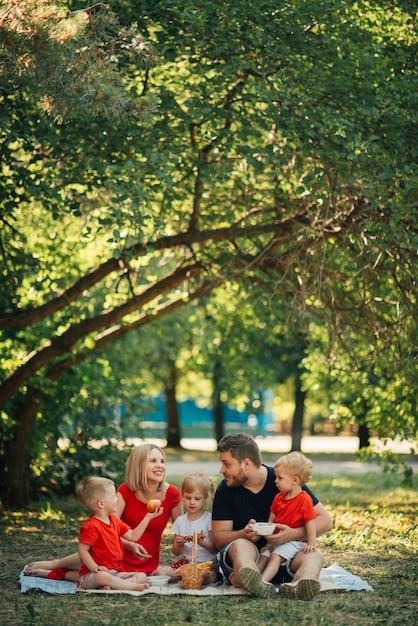 Famiglia che fa un picnic all'aperto con i loro bambini Foto Gratuite