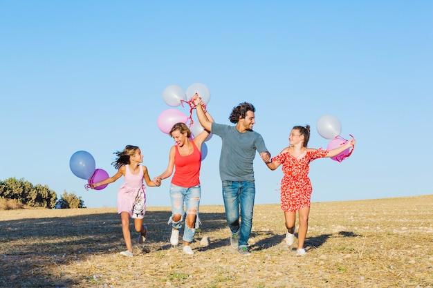 Famiglia che funziona nel campo e che tiene i palloni Foto Gratuite