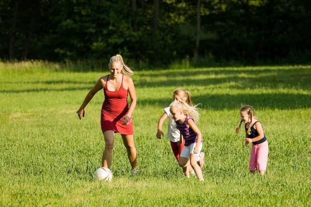 Famiglia che gioca a calcio in un campo di erba Foto Premium