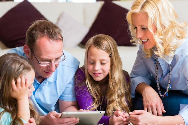 Famiglia che gioca con il computer della compressa a casa Foto Premium