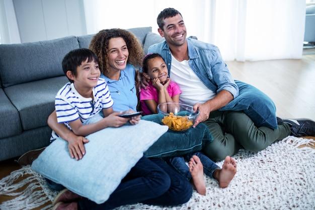 Famiglia che guarda la partita di football americano sulla televisione Foto Premium
