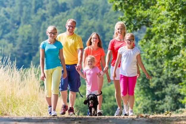 Famiglia che ha passeggiata sul sentiero nel bosco Foto Premium