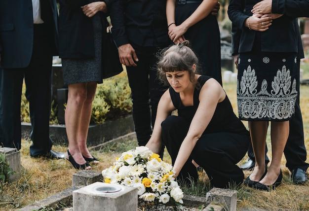 Famiglia che pone i fiori sulla tomba Foto Premium